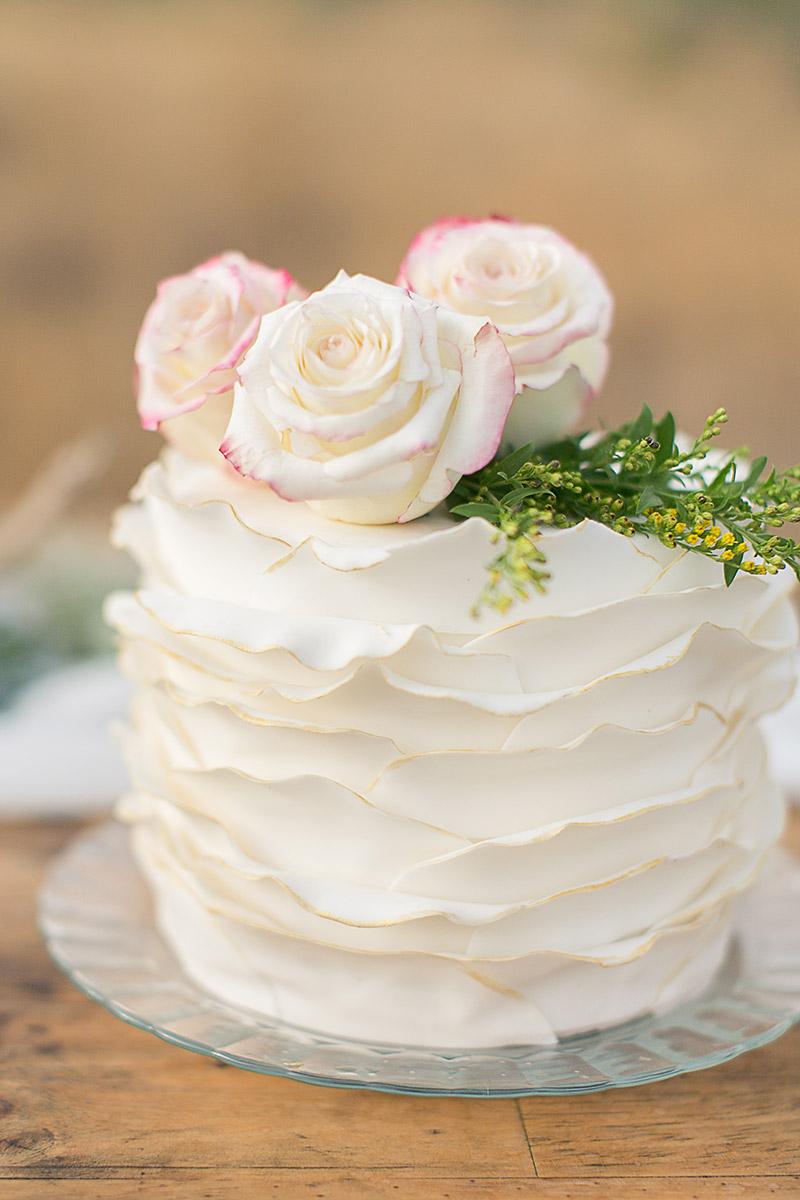 Hochzeitstorte mit Goldrand mit Rosen dekoriert. Ruffled Wedding cake