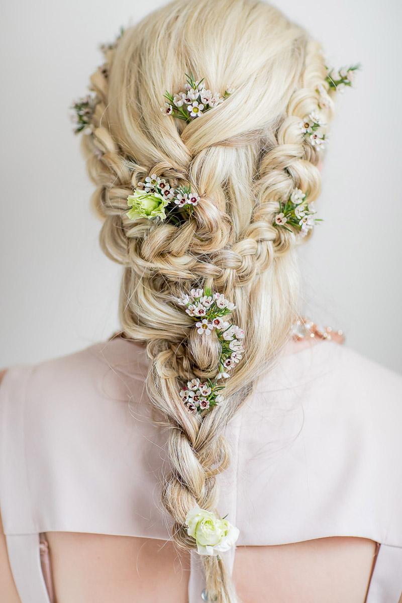 Brautfrisur geflochten mit frischen Blumen für lange Haare