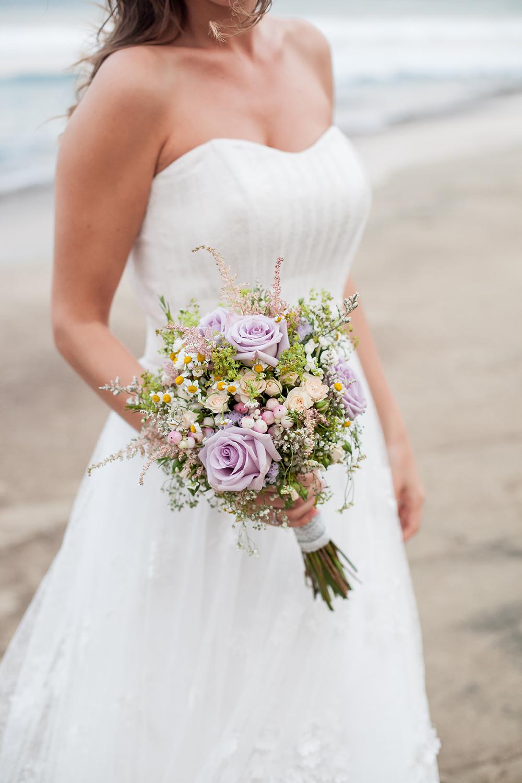Heiraten im Ausland, Brautpaarshooting am Meer. Brautstrauß mit Wiesenblumen in Pastell