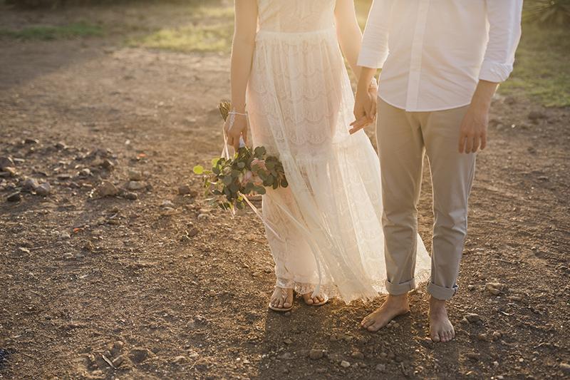 Heiraten am Strand mit den Füssen im Sand. Brautpaar boho